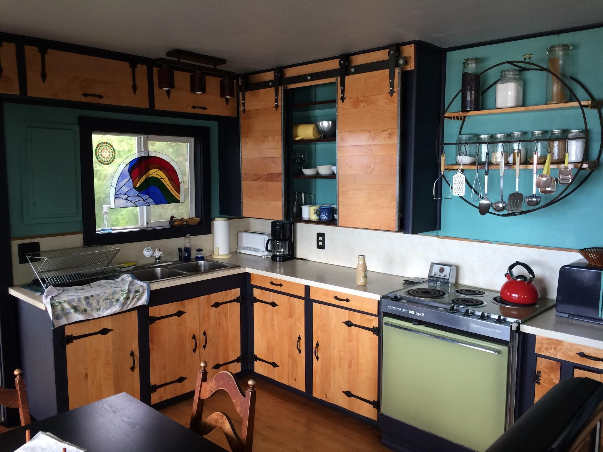 A colourful Airbnb kitchen with timber cupboards