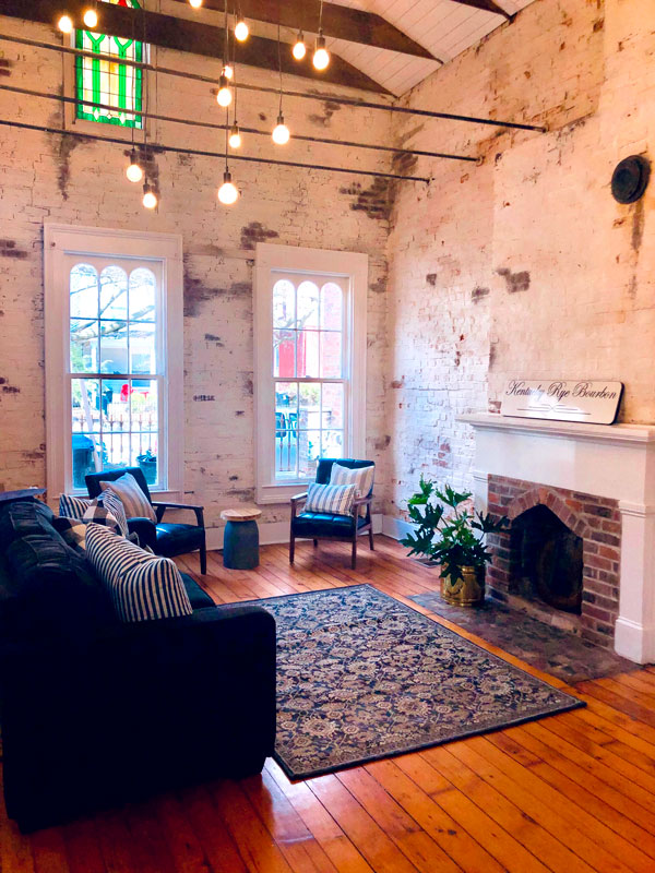 A high-ceilinged Airbnb living room with exposed walls and a firepalce. Source: /u/Agent_Oranged
